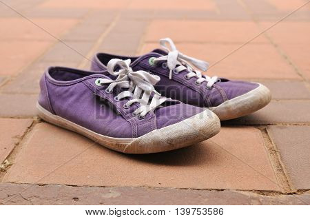 Old purple canvas shoes on the floor