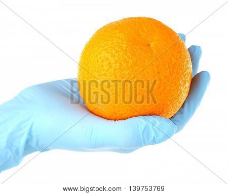 Allergy concept. Hand in blue glove holding orange isolated on white
