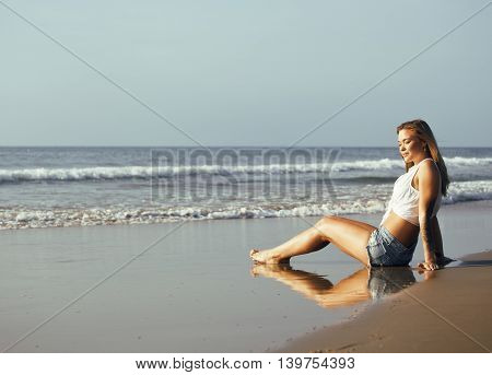 young pretty blond woman at seacoast walking relaxing, fashion lady at sunset, lifestyle people vacations concept