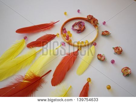 photo of a the process of creating handmade dreamcatcher with red and yellow feathers, pink and orange glass beads, red and orange paper flowers