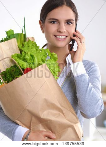 Woman with mobile phone holding shopping bag in kitchen