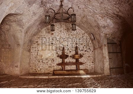 The gloomy atmosphere of the ancient dungeon. A low stone arch rough metal the lamp of the arch