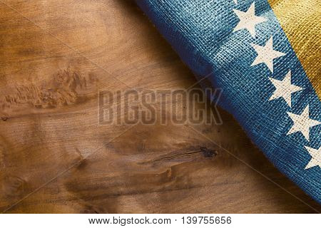 Fragment of Bosnia and Herzegovina flag on a wooden background.