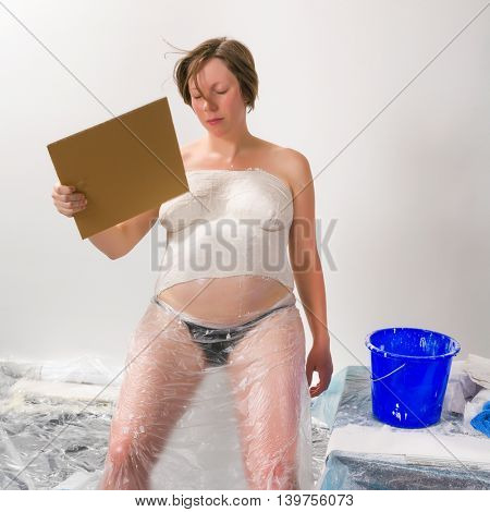 Pregnant young woman having a hot flash during the making of her plaster belly cast