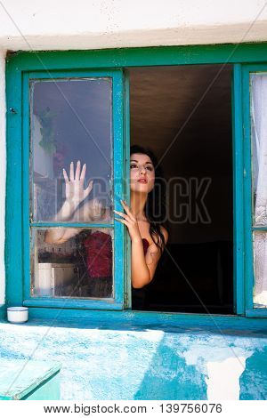 Sensual young lady waiting in the window of a derelict house