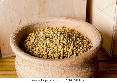 Mustard seeds with a wooden bowl on a wooden background