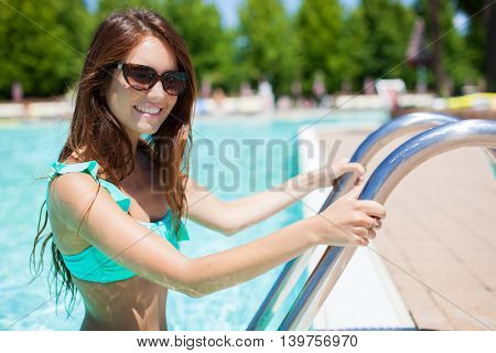 Beautiful woman coming out from the water of a swimming pool