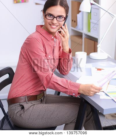 Young attractive female fashion designer working at office desk, drawing while talking on mobile.