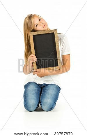 Young girl sitting on the floor with empty blackboard over white background