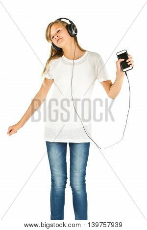Young girl standing listening to music on her smartphone over white background