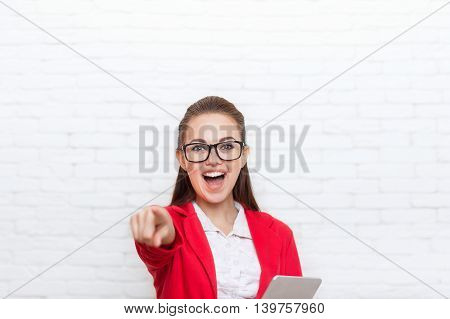Businesswoman happy excited laughing point finger at you wear red jacket glasses smile business woman over office wall