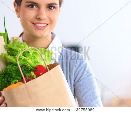 Happy young  woman with shopping bag full of vegetables,