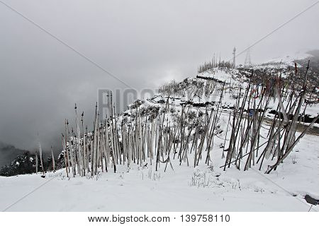 Prayer flags covering the top of snow mountains with the road in between