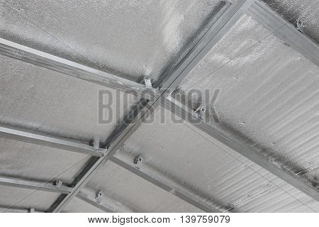 Suspended ceiling of the attic with reflective heat barrier.