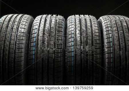 Stack of brand new high performance car tires on clean low-key black studio background