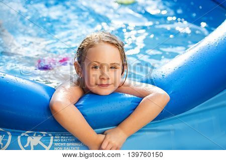 Portrait of cute little girl in blue big inflatable pool outdoors.