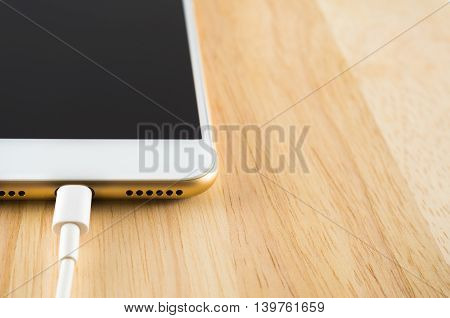 Close-up of gold smart phone charging with USB cable on wooden texture background Copy space