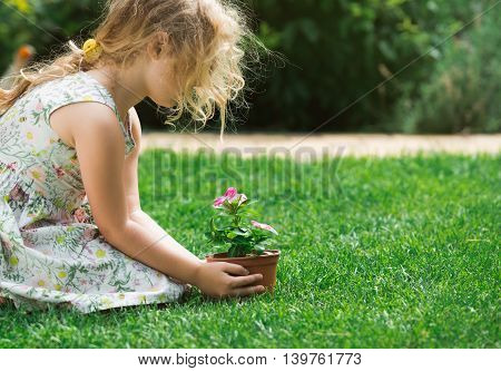 Little blonde girl holding young flower plant in hands on green background.