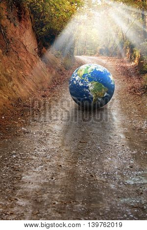 globe on dirt road in forest. Furnished NASA globe image used for this image.