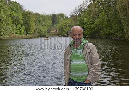 Middle-aged man in the background of the lake in the park