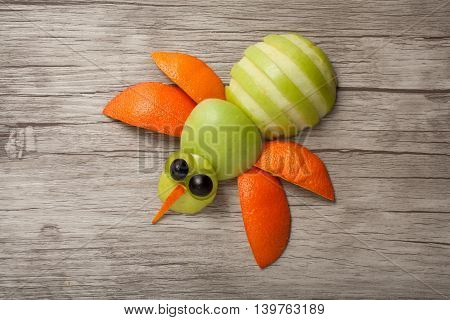 Funny bee made of fruits on board