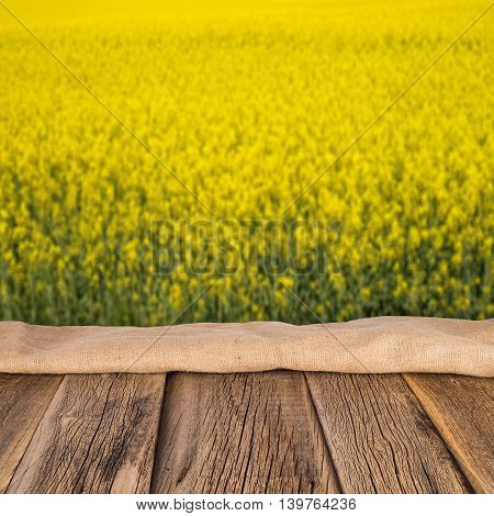 empty wooden planks with blurred background blooming yellow rape flowers