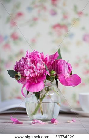 fresh bouquet of peonies in a glass jar on a white wooden table. book and a cup of teafresh bouquet of peonies in a glass jar on a white wooden table. book and a cup of tea