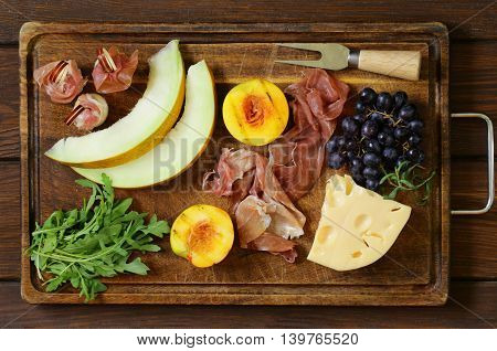 antipasti on a wooden board - prosciutto melone, ham with peaches, cheese and grapes