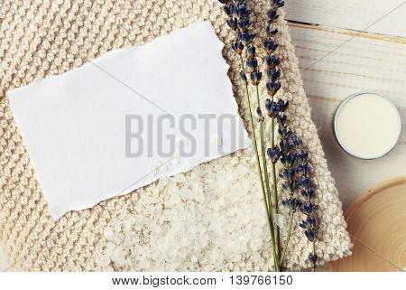 Paper spa invitation message on beige terry towel, aromatic lavender herb, body care cream, sea salt. Top view, warm toned.