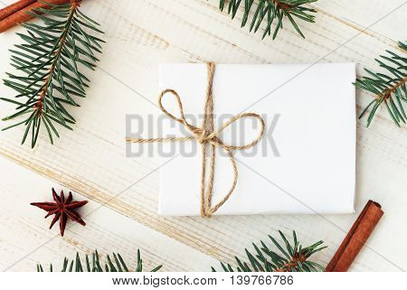 Handcrafted gift paper wrapping, decorated fir tree twigs, wintertime event congratulation. Top view.