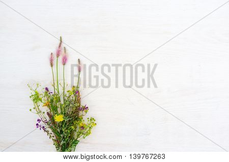 Spring flowers sheaf on white background, copyspace. Field plants on wooden backdrop