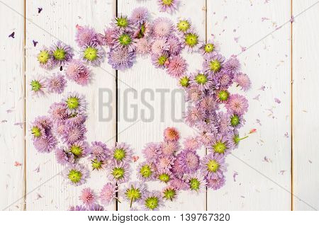 Circlet frame of purple flowers on white wooden background. Delicate romantic summer composition. Wedding style. Free space