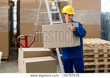 Female worker carrying a box in warehouse