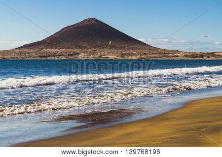 Big waves and brown-yellow sand on Playa el Medano beach Montana Roja mountain on blurred background Tenerife Canary islands Spain