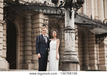 Beautiful wedding couple, bride, groom kissing and hugging against the background of theater.