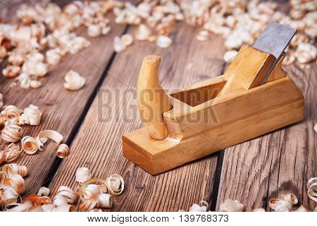 Wooden planer, table from old wood, a natural building material, handcrafted wood, ancient hand tools, carrying out carpentry, joinery tools, wood sawdust, old wood texture