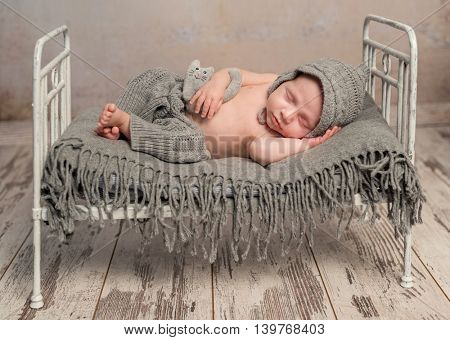 funny newborn baby in knitted hat and pants sleeping on old retro cot with plaid with hands behind head