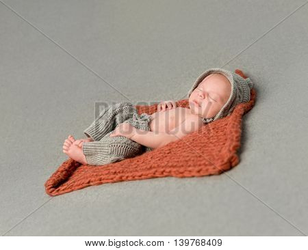 little newborn baby sleeping on knitted blanket top view