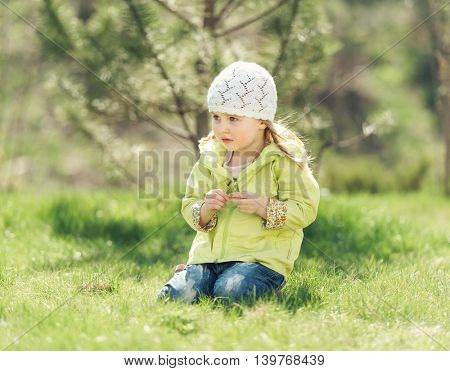smiling little girl in yellow coat sitting on a lawn in a park