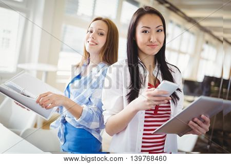 Portait of happy female colleagues holding files and mobile phone in creative office