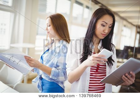 Female colleagues holding files and mobile phone in creative office