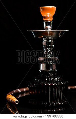 Deep red glass tobacco smoking hookah on the dark background.