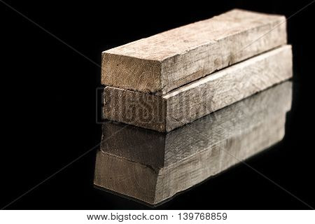 Cut timber bars for construction isolated on black background