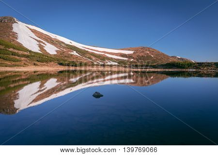 Mountain Lake. Spring landscape on a sunny day. Last snow on the slopes. Reflection of the hills in the water. Carpathian, Ukraine, Europe