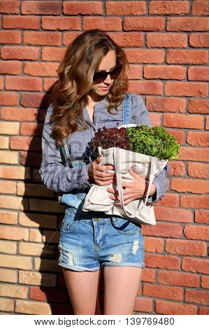 Stylish Woman Is Holding In Their Hands A Linen Bag Full Of Fresh Lettuce Salad