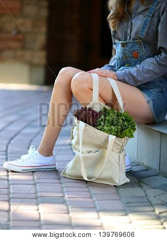 Lettuce. Linen Bag Full Of Fresh Salad Stands Near The Legs Of Stylish Woman