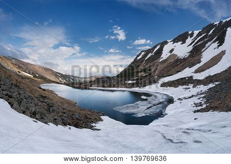 Spring landscape. Mountain lake with ice and snow on the shore. Overcast day. Carpathians, Ukraine, Europe