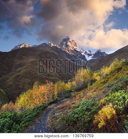 Autumn landscape. Path in the mountains. Mount Ushba, Main Caucasian ridge. Zemo Svaneti, Georgia