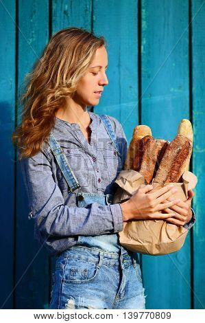 French Baguette. Blonde Woman Is Holding In Their Hands A Paper Bag With Baguettes