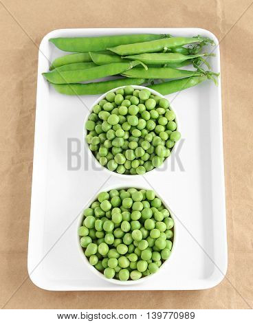 Healthy food pea, which has vitamins and minerals, in two bowls and pea pods.